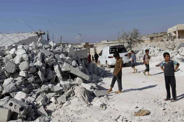Residents inspect damaged buildings in what activists say was a U.S. airstrike in Kfredrian, Idlib province in Syria, Tuesday, Sept. 23, 2014. (Reuters/Abdalghne Karoof)