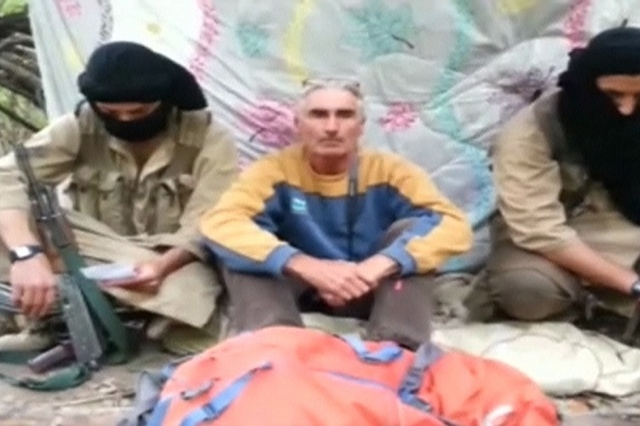 A man who identified himself as Herve Gourdel sits in between two masked gunmen in this file still image taken from video which was published on the Internet on September 22, 2014. (REUTERS/The Ca ...