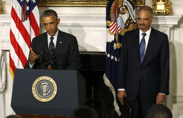 U.S. President Barack Obama, left, announces the resignation of Attorney General Eric Holder in the White House State Dining Room in Washington, Thursday, Sept. 25, 2014. (Reuters/Larry Downing)