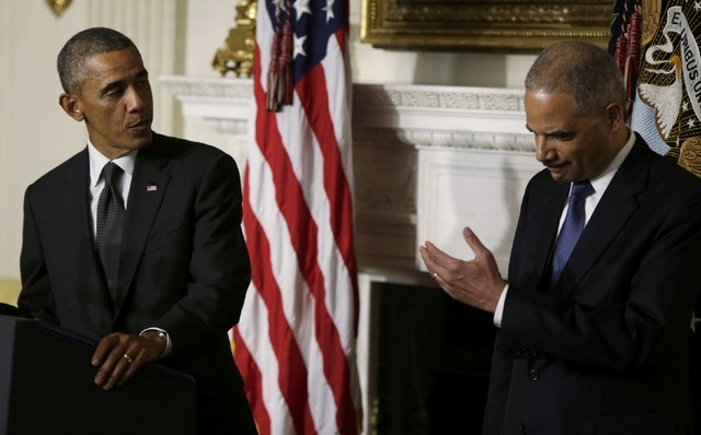 U.S. President Barack Obama, left, turns to Attorney General Eric Holder as he announces Holder's resignation in the White House State Dining Room in Washington, Thursday, Sept. 25, 2014. (Reuters ...