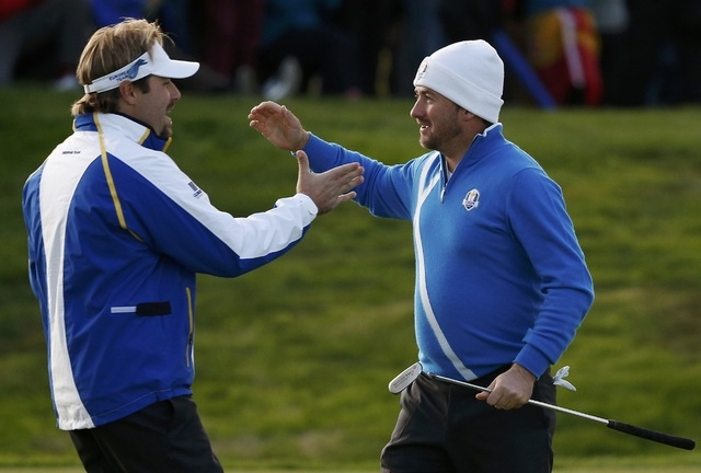 European Ryder Cup players Victor Dubuisson, left, and Graeme McDowell celebrate on the 17th green after winning their foursomes 40th Ryder Cup match at Gleneagles in Scotland September 26, 2014.  ...