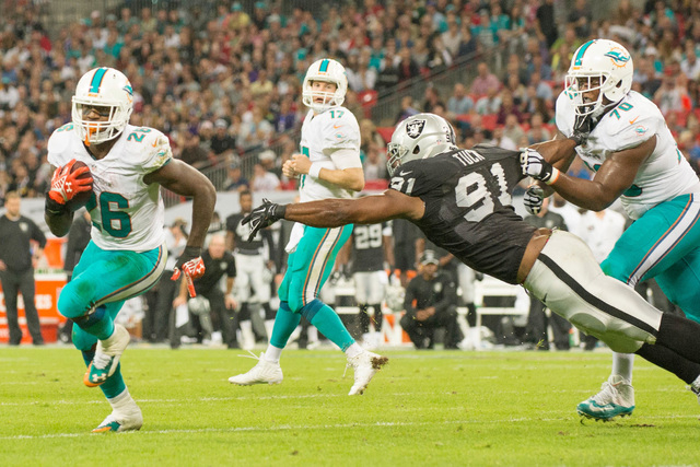 Sep 28, 2014; London, UNITED KINGDOM;  Miami Dolphins running back Lamar Miller (26) carries the ball in front of Oakland Raiders defensive end Justin Tuck (91) to score a touchdown in the second  ...