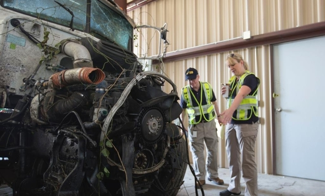 Investigator-in-charge Jennifer Morrison, right, and NTSB Board Member Robert Sumwalt view the wreckage of a bus crash near Davis, Oklahoma, in this undated handout photo provided by the National  ...