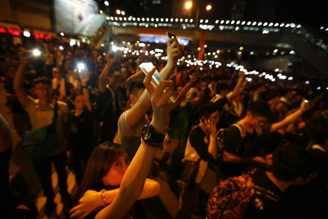 Protesters hold up their mobile phones with the flash light function switched on, as they block the main street to the financial Central district, outside the government headquarters in Hong Kong  ...
