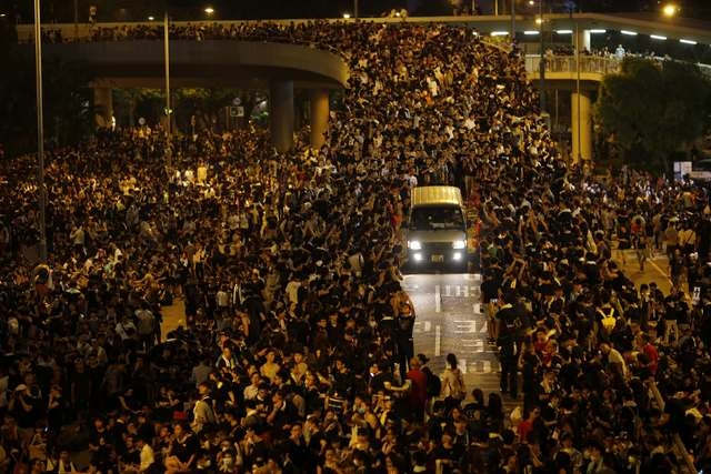 A vehicle drives among protesters blocking the main street to the financial Central district, outside the government headquarters, in Hong Kong September 29, 2014. (REUTERS/Carlos Barria)