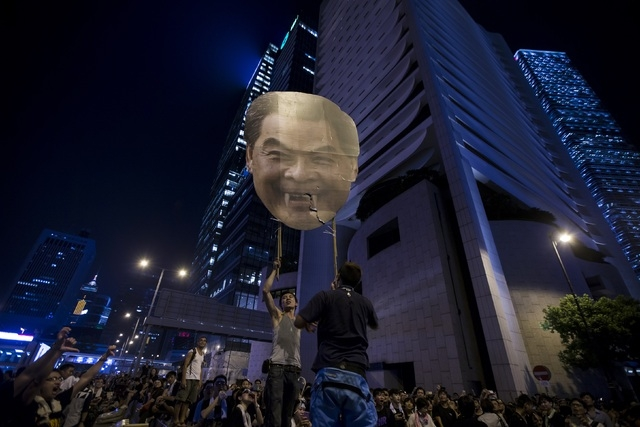 Protesters carry a defaced cutout of Hong Kong Chief Executive Leung Chun-ying, as they protest near the central government offices in the business district of Admiralty in Hong Kong September 29, ...