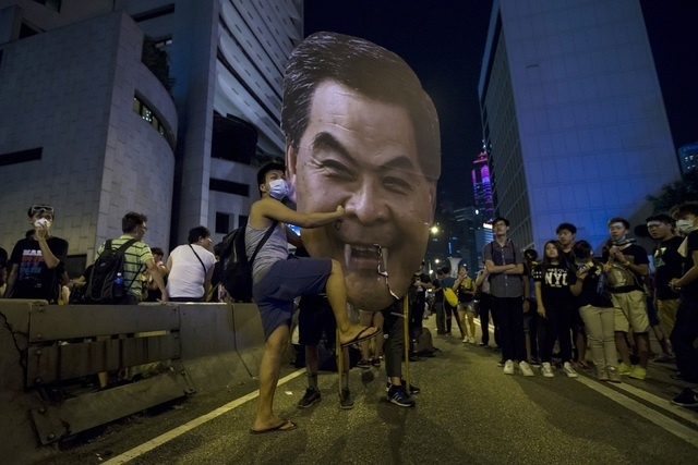 A protester hits a defaced cutout of Hong Kong Chief Executive Leung Chun-ying, as they protest near the central government offices in the business district of Admiralty in Hong Kong September 29, ...