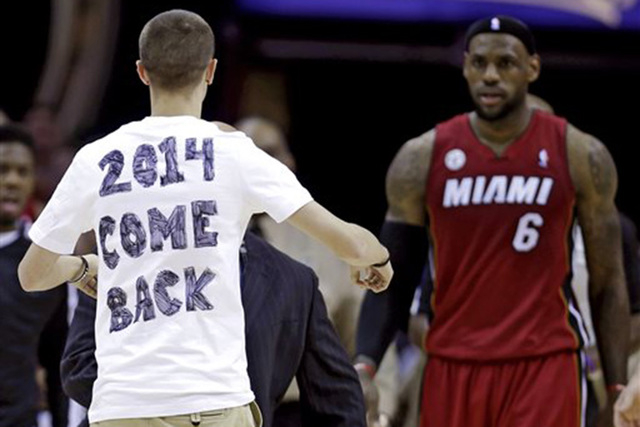 In this Wednesday, March 20, 2013 file photo, a fan runs out on the court towards Miami Heat's LeBron James during the fourth quarter of an NBA basketball game against the Cleveland Cavaliers in C ...