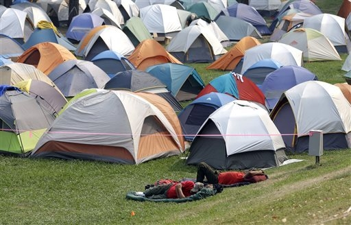 A pair of firefighters sleep out in the open near dozens of tents used to house personnel coming off the fire lines from the King Fire, at the base camp in Placerville, Calif., Friday, Sept. 19, 2 ...