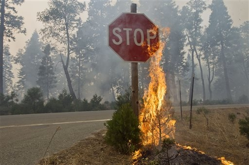 Fire burns near a 'Stop' sign  near Uncle Tom's Cabin in El Dorado County on Thursday,  Sept. 18, 2014. The King fire has burned over 70,000 acres. The wind-whipped fire burned through 114 square  ...