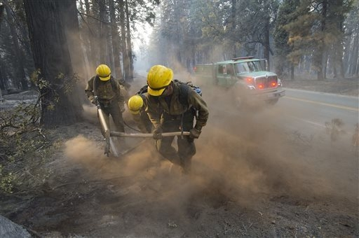 U.S. Forest Service crews from Plumas County clean up along Wentworth Springs Road near Uncle Tom's Cabin in El Dorado County on Thursday, Sept. 18, 2014. The wind-whipped fire burned through 114  ...