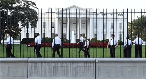 Uniformed Secret Service officers walk along the fence on the North side of the White House in Washington, Saturday, Sept. 20, 2014.   The Secret Service is coming under intense scrutiny after a m ...