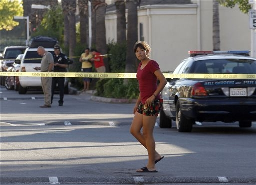 Neighbors stand behind police lines as police officers block the scene of a shooting in Bell Gardens, Calif., Tuesday, Sept. 30, 2014. Bell Gardens mayor Daniel Crespo was shot to death Tuesday du ...