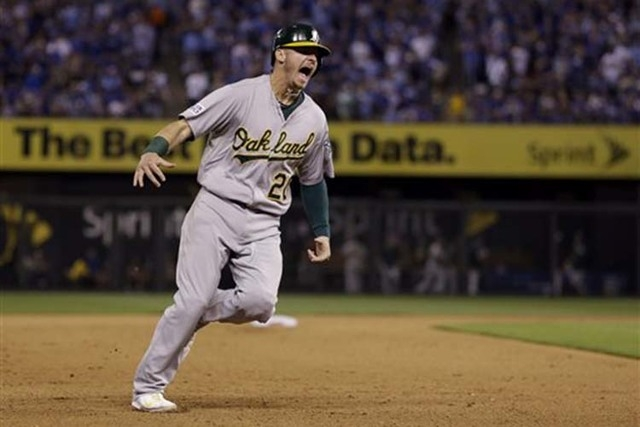 Oakland Athletics' Josh Donaldson celebrates as he rounds the bases on a three-run home run by teammate Brandon Moss during the sixth inning of the AL wild-card playoff baseball game against the K ...