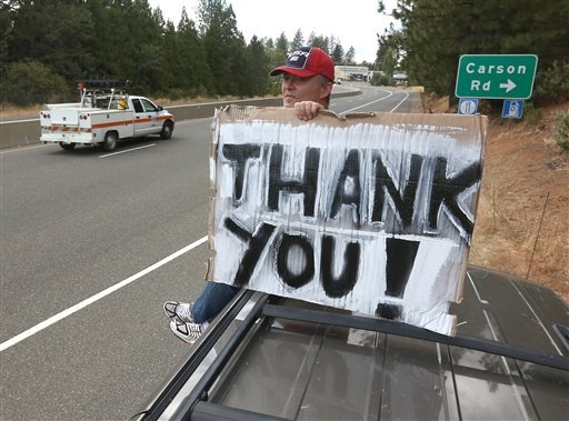 Herve Leconte sits atop his vehicle to display a sign thanking all those who are dealing with the King fire while park alongside Highway 50 near Camino, Calif., Thursday, Sept. 18, 2014. (AP Photo ...
