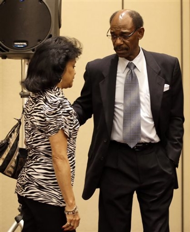 Former Texas Rangers manager Ron Washington escorts his wife Gerry, left, away after Washington made a statement at a news conference, Thursday, Sept. 18, 2014, in Irving, Texas. (AP Photo/Tony Gu ...