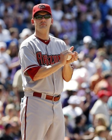 In this May 27, 2010, file photo, Arizona Diamondbacks manager A.J. Hinch rubs a baseball after pulling starting pitcher Dan Haren in the seventh inning of baseball game against the Colorado Rocki ...