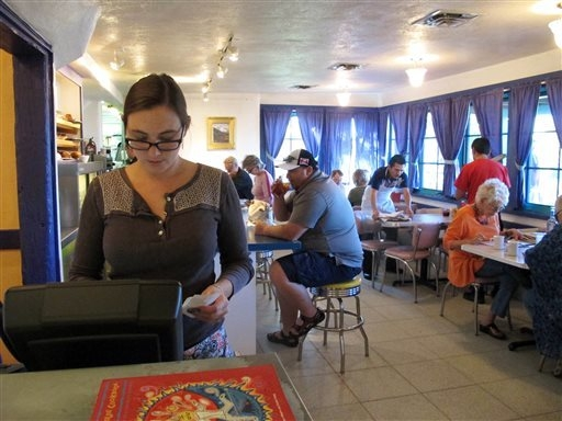 A hostess at the cashier as customers dine at Harry's Roadhouse, a diner that is a favorite among locals. (AP Photo/Jeri Clausing)