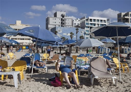 People enjoy the beach on the Mediterranean Sea in Tel Aviv, Israel. 2014 was supposed to be a record-breaking year for tourist visits to Israel. But all that changed when this summers 50-day war  ...