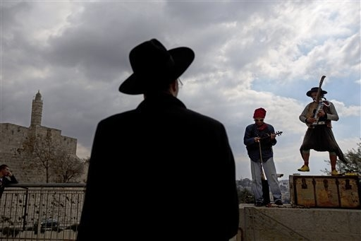 An ultra-Orthodox Jewish man looks at street performers as the play music near the Tower of David in Jerusalem's Old City. 2014 was supposed to be a record-breaking year for tourist visits to Isra ...