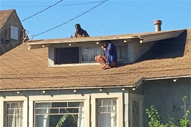 In this Wednesday, Sept. 24, 2014 photo, Laura Rivera, who fled her house through an attic window to escape an intruder, seen on the roof behind her, waits for help after an early-morning break in ...