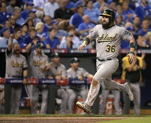Oakland Athletics' Derek Norris runs home to score on a single by Coco Crisp during the sixth inning of the AL wild-card playoff baseball game against the Kansas City Royals on Tuesday, Sept. 30,  ...