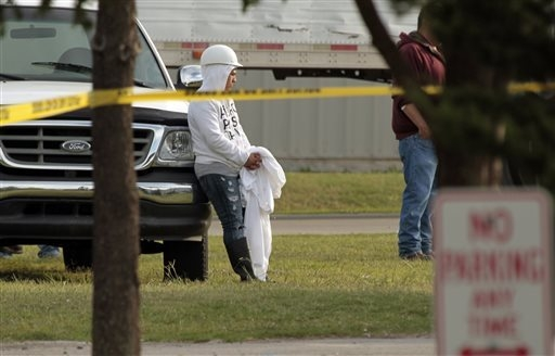 Employees wait in the parking lot as police investigate a shooting at Vaughn Foods on Thursday, Sept. 25, 2014 in Moore, Oklahoma. Police said Friday, Sept. 26, a man who had been fired from the f ...