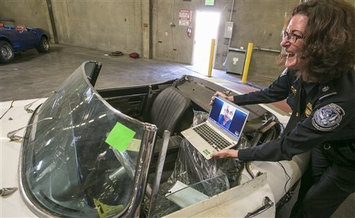 Lee Ann Harty, U.S. Customs and Border Protection public affairs liaison chief, uses a laptop computer to show the interior of a 1967 Jaguar XK-E convertible that was stolen 46 years ago to his or ...