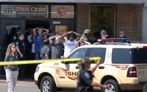 Students put their hands on their heads as they are lead out of Fern Creek High School in Louisville, Ky. on Tuesday, Sept. 30 2014 after a shooting. Officials said a student was injured and one p ...