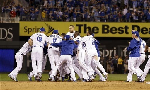 Kansas City Royals mob teammate Salvador Perez after he hit a walk-off single in the 12th inning to defeat the Oakland Athletics 9-8 in the AL wild-card playoff baseball game Tuesday, Sept. 30, 20 ...