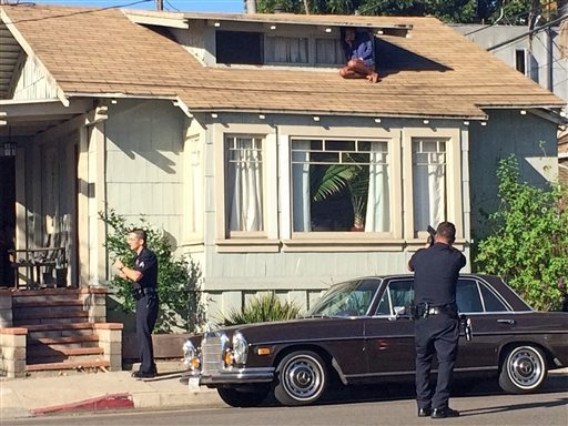 CORRECTS NAME FROM LAURA RIVERA TO MELORA RIVERA -  In this Wednesday, Sept. 24, 2014 photo, Melora Rivera, who fled her house through an attic window to escape an intruder, waits for help as Los  ...
