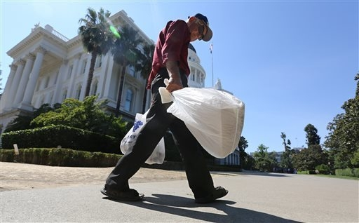 Plastic single-use bags are carried past the state Capitol in Sacramento, California, Aug. 12, 2014. Gov Jerry Brown signed SB270 on Tuesday, Sept. 30, 2014, which imposes the nation's first state ...