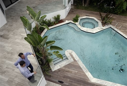 Developer Michael Capponi, left, talks with real estate broker Massimo Nicastro of South Beach Estates at a waterfront property he renovated during a viewing for brokers in Miami Beach, Florida, S ...