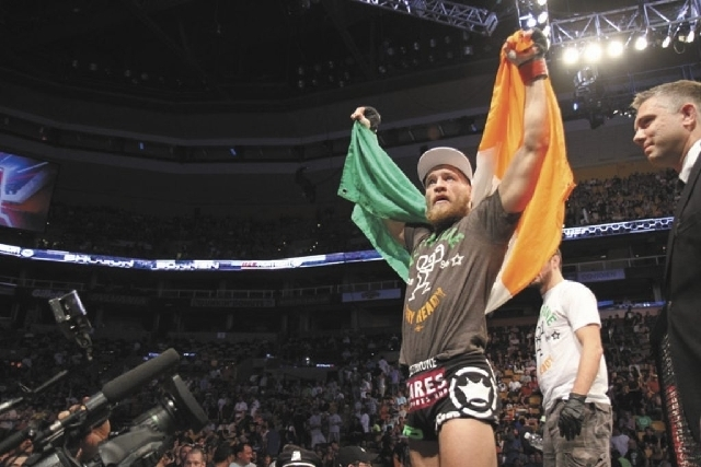 Conor McGregor, of Ireland, leaves the ring draped in an Irish flag after beathing Max Holloway in their UFC on Fox Sports 1 mixed martial arts bout in Boston, Saturday, August 17,2013. McGregor w ...
