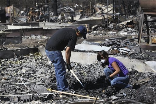 Jose Tapia and his wife, Chela Tapia look for his wedding ring and items that belonged to her mother Thursday, Sept. 18, 2014, in the ashes of their home in the Angel Valley neighborhood in Weed,  ...