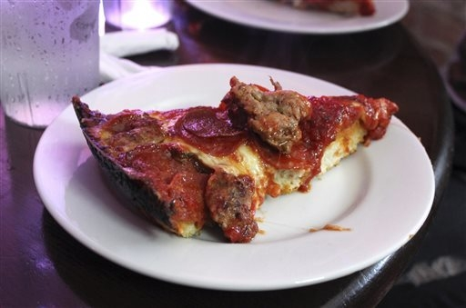 In this Sept. 5, 20143 photo, a slice of deep-dish pizza is shown at Pequod's in Chicago. Chicago is one of a handful of cities across the country, like Boston, Milwaukee and New York, with compan ...