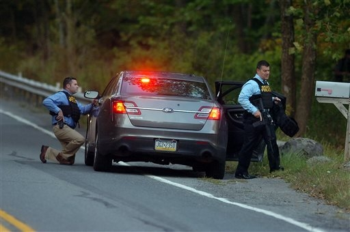 Pennsylvania State Police officers move quickly with their weapons on Route 447 in Price Township on Sunday, Sept. 21, 2014 in Canadensis, Pa., during the massive search for suspected killer Eric  ...