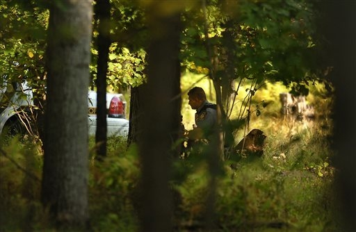 A Pennsylvania State Trooper sits in the woods with his weapon ready, near Snow Hill Road in Price Township on Sunday, Sept. 21, 2014 near Canadensis, Pa., during the massive search for suspected  ...