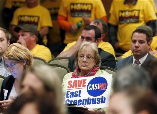 Marie Cookson of East Greenbush, N.Y., holds a sign opposing a casino in her town during a public meeting on casinos on Monday, Sept. 22, 2014, in Albany, N.Y. Supporters and critics of proposals  ...