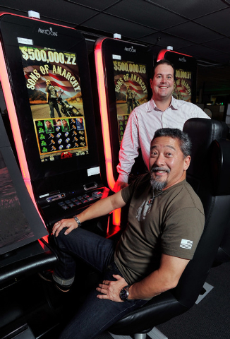 """Aristocrat's Ted Hase, front, vice president of R&D global games and Dallas Orchard, vice president of gaming operations, pose next to the upcoming slot machine, """"Son of Anarchy,"""" based on the net ..."""