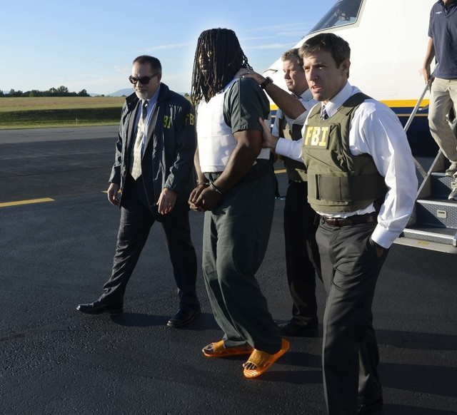 FBI agents escort Jesse Leroy Matthew Jr., center, from a plane during extradition to Charlottesville, Virginia, on Friday, Sept. 26, 2014. Matthew, 32, is suspect in the Sept. 13, 2014, disappear ...