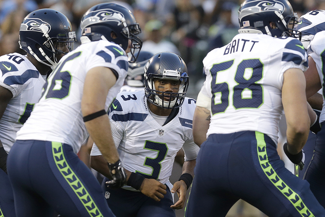 Seattle Seahawks quarterback Russell Wilson, center, huddles with teammates during the first half of an NFL preseason football game against the Oakland Raiders in Oakland, Calif., Thursday, Aug. 2 ...