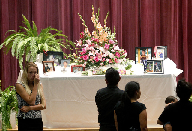 Mourners look at a display of photos during a memorial service at Bell High School for the victims of Thursday's shootings on Sunday, Sept. 21, 2014 in Bell, Fla. Police say Don Spirit shot and ki ...