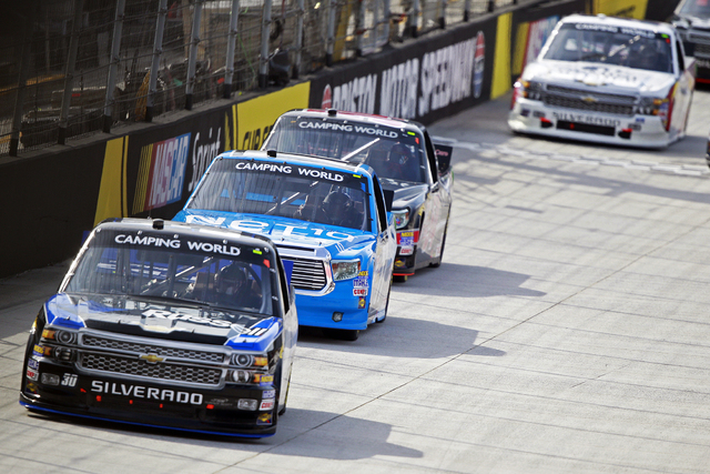 Driver Ron Hornaday Jr. (30) leads driver German Quiroga (77) and others during the NASCAR UNOH 200 Truck Series auto race on Thursday, Aug. 21, 2014, in Bristol, Tenn. (AP Photo/Wade Payne)