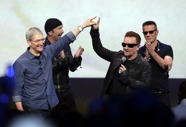 Apple CEO Tim Cook, left, greets Bono from the band U2 after they preformed at the end of the Apple event on Tuesday, Sept. 9, 2014, in Cupertino, Calif. Apple unveiled a new Apple Watch, the iPho ...