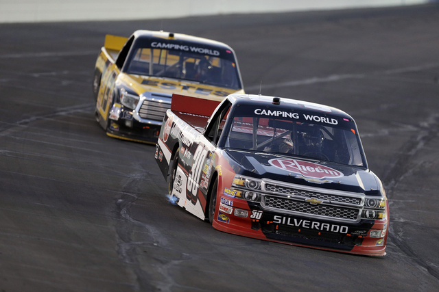 Driver Ron Hornaday Jr., front, leads Jeb Burton during the Drivin' for Linemen 200 NASCAR Truck Series auto race at Gateway Motorsports Park Saturday, June 14, 2014, in Madison, Ill. (AP Photo/Je ...