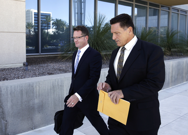 Suspended Las Vegas area family court judge Steven Jones, right, walks out of federal court with his attorney Robert Draskovich Wednesday, Sept. 17, 2014, in Las Vegas. Jones pleaded guilty to one ...