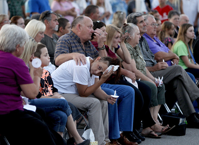 Mourners sitting in the section reserved for family are seen during a candlelight vigil at Bell Elementary for the victims of Thursday's shootings on Sunday, Sept. 21, 2014 in Bell, Fla. (AP Photo ...