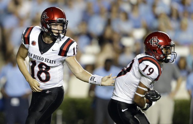 San Diego State quarterback Quinn Kaehler (18) hands off to Donnel Pumphrey (19) during the first half of an NCAA college football game in Chapel Hill, N.C., Saturday, Sept. 6, 2014. (AP Photo/Ger ...
