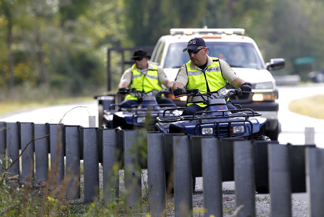 Albemarle County Police riding all-terrain vehicles perform a search along the edge of Monacan Trail Road on Sunday, Sept. 28, 2014. Hannah Elizabeth Graham, 18, a second-year University of Virgin ...